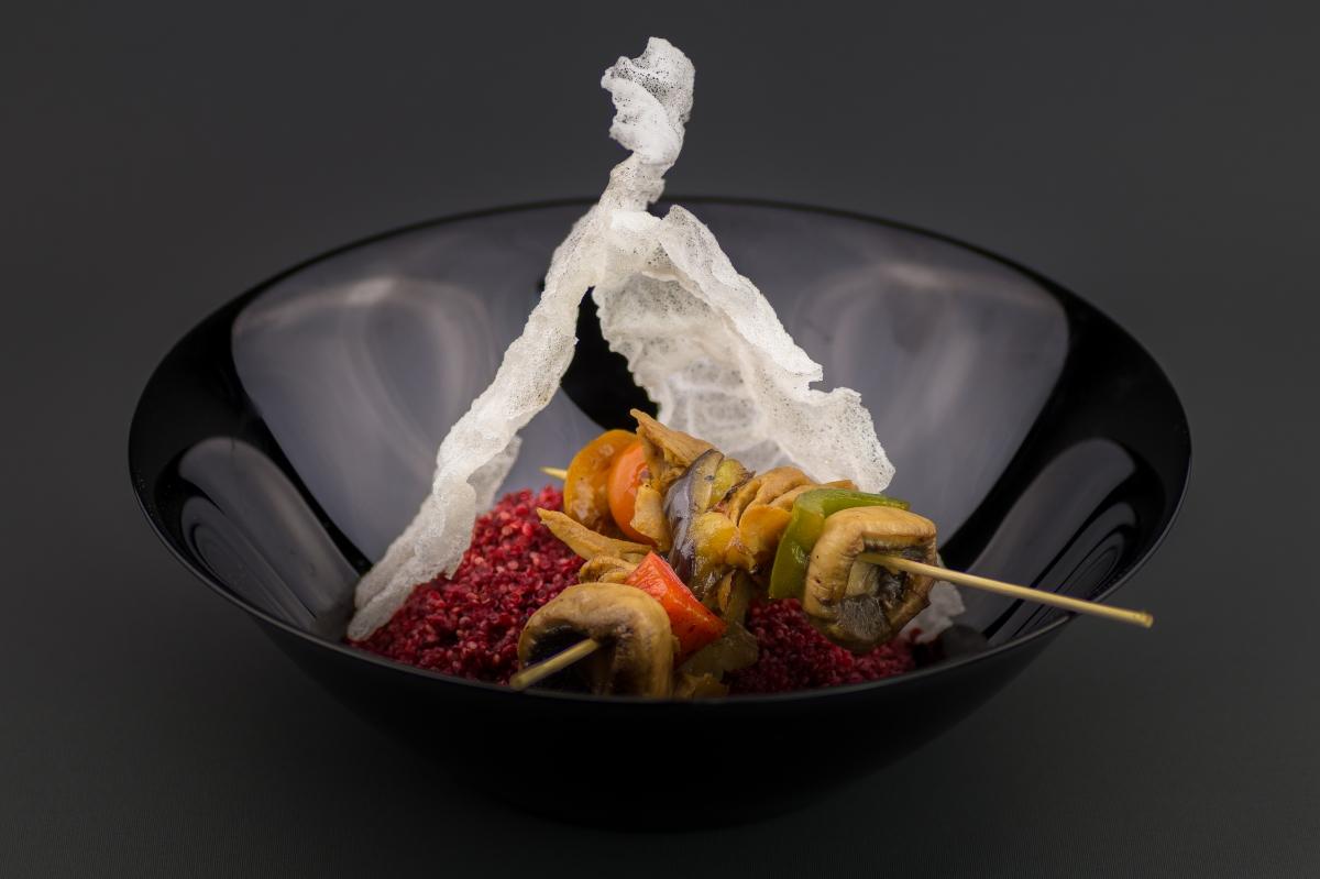 Brochetas de verdura sobre nido de quinoa roja